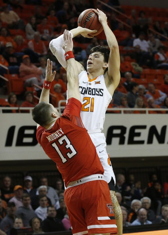 Oklahoma State guard Lindy Waters III (21) shoots over Texas Tech guard Matt Mooney (13) in the first half of an NCAA college basketball game in Stillwater, Okla. (AP Photo/Sue Ogrocki)