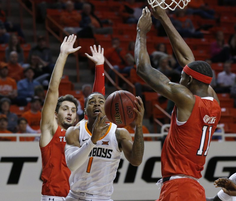 Oklahoma State guard Curtis Jones, center, goes to the basket between Texas Tech guard Davide Moretti, left, and forward Tariq Owens, right, in the first half of an NCAA college basketball game in Stillwater, Okla. (AP Photo/Sue Ogrocki)