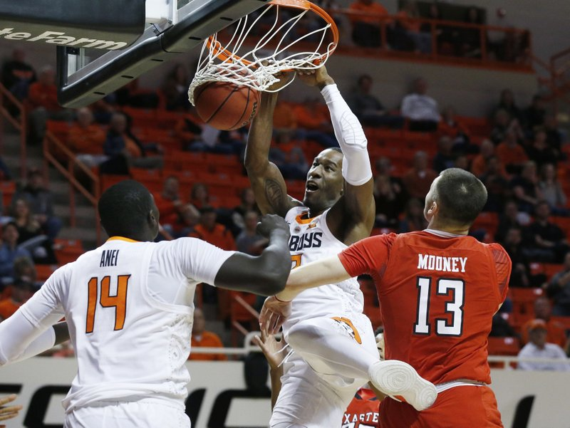 Oklahoma State forward Cameron McGriff, center, dunks in front of teammate Yor Anei,left, and Texas Tech guard Matt Mooney, right,  in the first half of an NCAA college basketball game in Stillwater, Okla. (AP Photo/Sue Ogrocki)