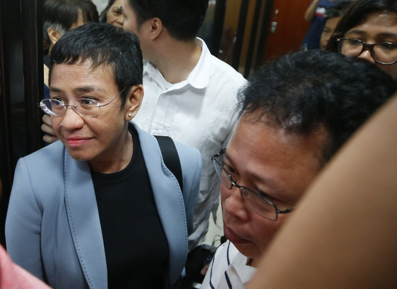 Maria Ressa, the award-winning head of a Philippine online news site Rappler that has aggressively covered President Rodrigo Duterte's policies, is escorted into another room following her arrest by National Bureau of Investigation agents in a libel case Wednesday, Feb. (AP Photo/Bullit Marquez)