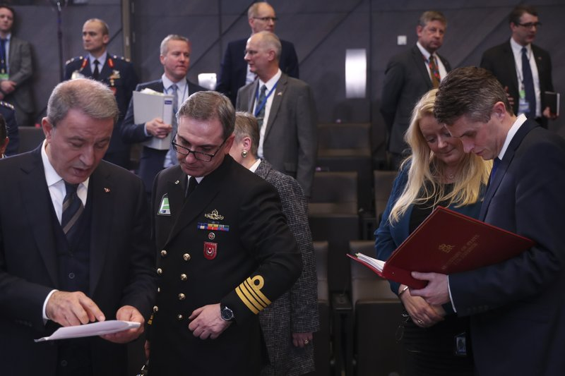 Britain's Defence Minister Gavin Williamson, right, and Turkey's Defence Minister Hulusi Akar, left, check papers during a meeting of NATO defence ministers at NATO headquarters in Brussels, Wednesday, Feb. (AP Photo/Francisco Seco)