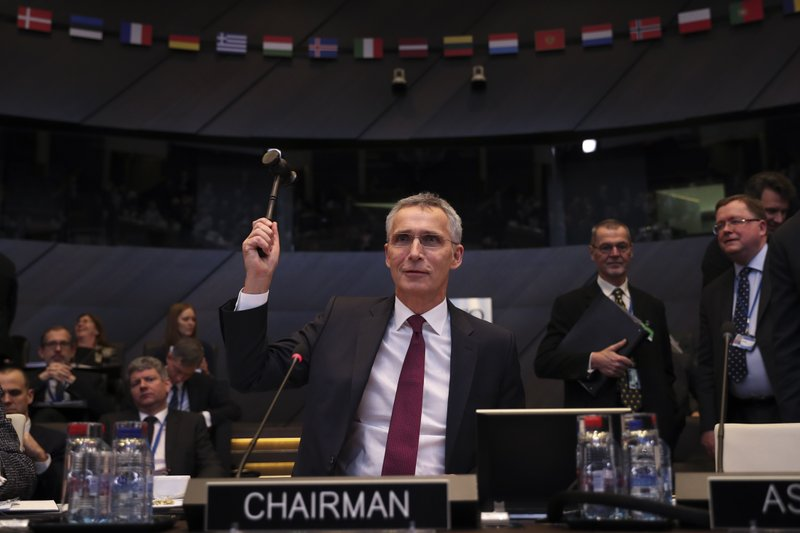 NATO Secretary General Jens Stoltenberg bangs a gavel to signal the start of a meeting of NATO defence ministers at NATO headquarters in Brussels, Wednesday, Feb. (AP Photo/Francisco Seco)