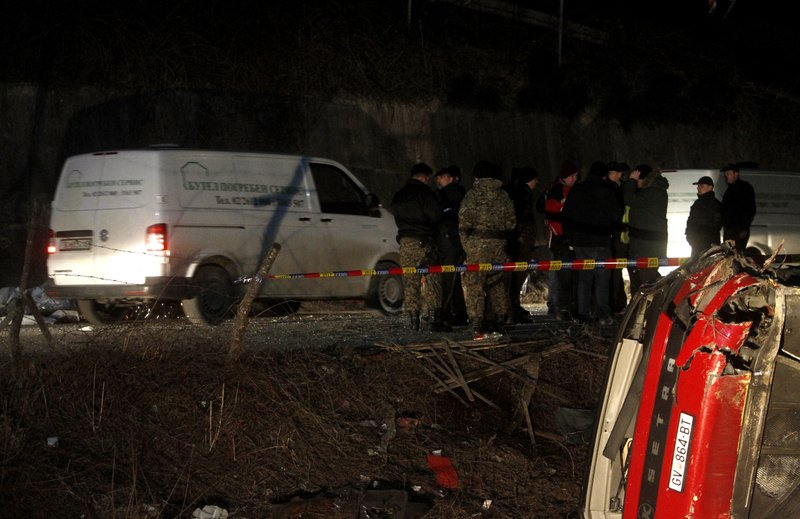 Police and investigators stand near the bus wreckage at the crash site at the village of Laskarci, west of Skopje, North Macedonia, Wednesday, Feb. (AP Photo/Boris Grdanoski)