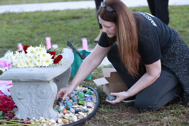 Suzanne Devine Clark, an art teacher at Deerfield Beach Elementary School, places painted stones at a memorial outside Marjory Stoneman Douglas High School during the one-year anniversary of the school shooting, Thursday, Feb. (AP Photo/Wilfredo Lee)