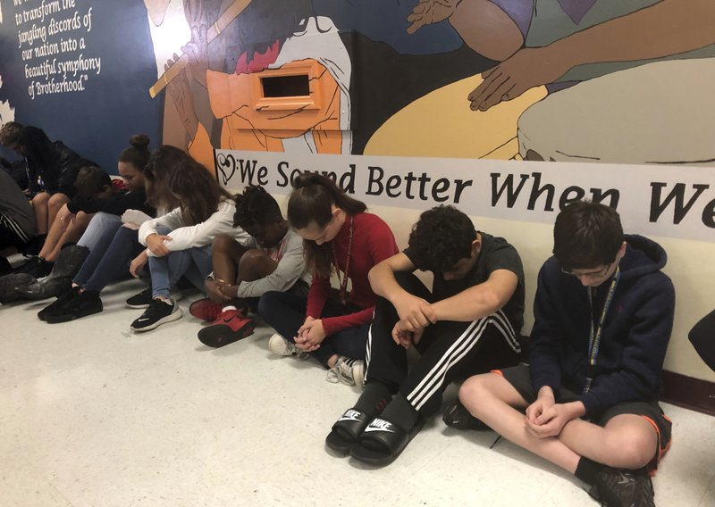 Students at Seminole Middle School in Plantation, Fla., participate in a moment of silence Thursday, Feb. (AP Photo/Terry Spencer)