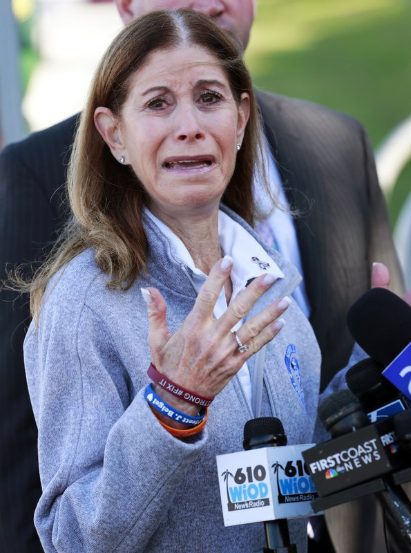 Linda Beigel Schulman, mother of Scott Beigel, a geography teacher and cross country coach who was killed during the Marjory Stoneman Douglas High School shooting last year, gestures as she speaks to members of the media during the one-year anniversary of the deadly shooting, Thursday, Feb. (AP Photo/Wilfredo Lee)