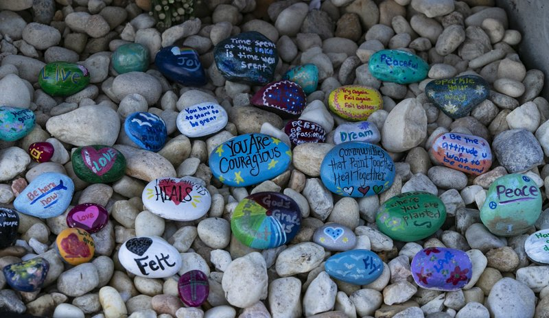 Stones are placed at a memorial outside Marjory Stoneman Douglas High School during the one-year anniversary of the school shooting, Thursday, Feb. (Al Diaz/Miami Herald via AP)
