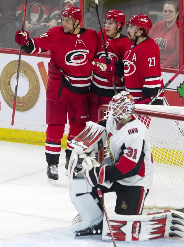 Ottawa Senators goaltender Anders Nilsson (31) kneels in his crease as Carolina Hurricanes right wing Nino Niederreiter (21) and defenseman Justin Faulk (27) celebrate a goal by left wing Teuvo Teravainen (86) during the third period of an NHL hockey game, Tuesday, Feb. (Adrian Wyld/The Canadian Press via AP)