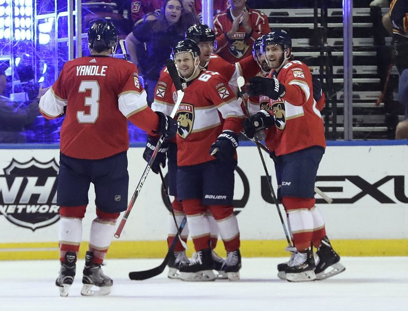 Florida Panthers right wing Evgenii Dadonov, center, celebrates with teammates after scoring during the second period of an NHL hockey game against the Calgary Flames on Thursday, Feb. (AP Photo/Brynn Anderson)