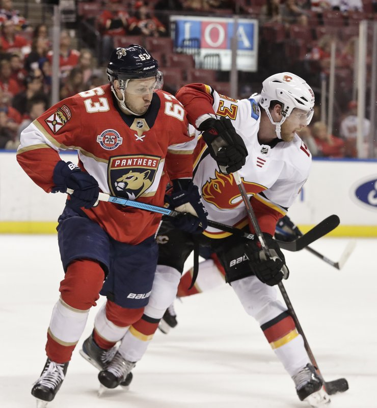 Florida Panthers right wing Evgenii Dadonov and Calgary Flames center Sam Bennett both go for the puck during the second period of an NHL hockey game Thursday, Feb. (AP Photo/Brynn Anderson)