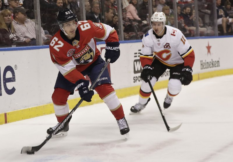 Florida Panthers center Denis Malgin skates with the puck against Calgary Flames center Mikael Backlund during the first period of an NHL hockey game Thursday, Feb. (AP Photo/Brynn Anderson)