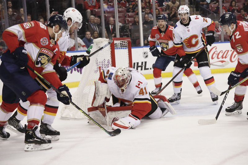 Calgary Flames goaltender Mike Smith catches the puck in front of Florida Panthers center Aleksander Barkov during the first period of an NHL hockey game Thursday, Feb. (AP Photo/Brynn Anderson)