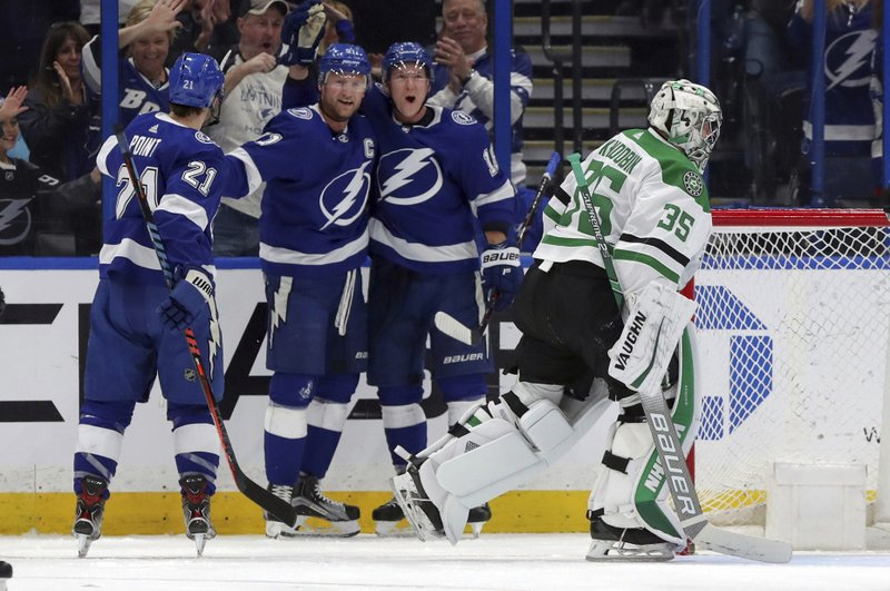 Dallas Stars goaltender Anton Khudobin, of Kazakhstan, reacts as members of the Tampa Bay Lightning, from left, Brayden Point, Steven Stamkos, and Ondrej Palat, of the Czech Republic, celebrate a goal during the first period of an NHL hockey game Thursday, Feb. (AP Photo/Mike Carlson)