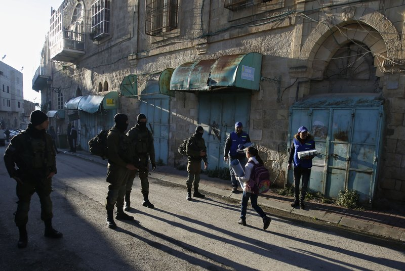 In this Tuesday, Feb. 12, 2019 photo, Palestinian observers, right, watch as children walk past Israeli soldiers on their way to school in the West Bank city of Hebron. (AP Photo/Majdi Mohammed)