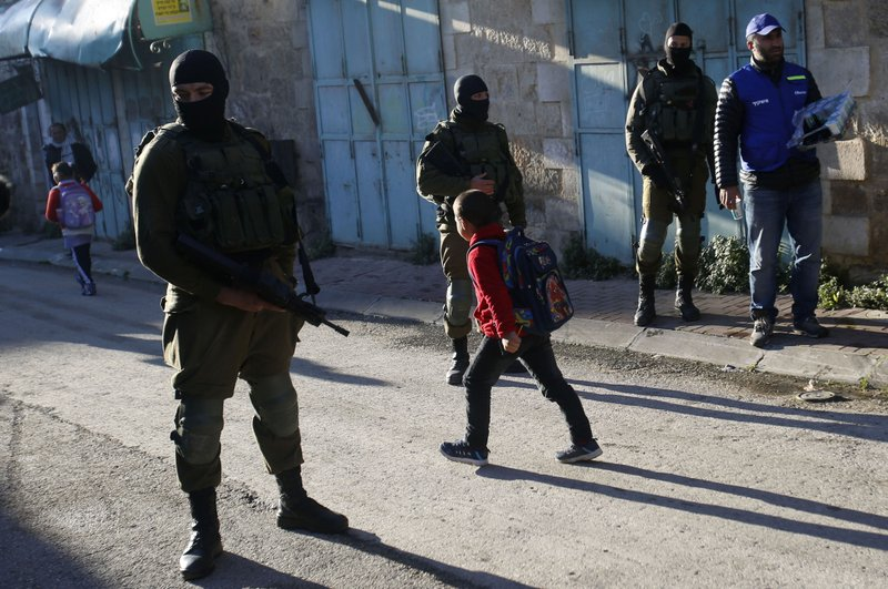 In this Tuesday, Feb. 12, 2019 photo, A Palestinian observers, right, watches as children walk past Israeli soldiers on their way to school in the West Bank city of Hebron. (AP Photo/Majdi Mohammed)