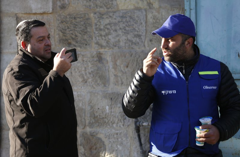 In this Tuesday, Feb. 12, 2019 photo, an Israeli settler, left, takes a picture of a Palestinian observer as he watches over children walking to school in the West Bank city of Hebron. (AP Photo/Majdi Mohammed)