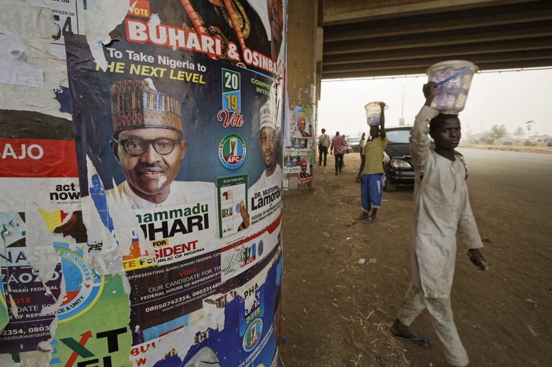 The face of incumbent President Muhammadu Buhari is seen on a campaign poster fixed to the pillars of a highway bridge near Nyanya, on the eastern outskirts of the capital Abuja, Nigeria Tuesday, Feb. (AP Photo/Ben Curtis)