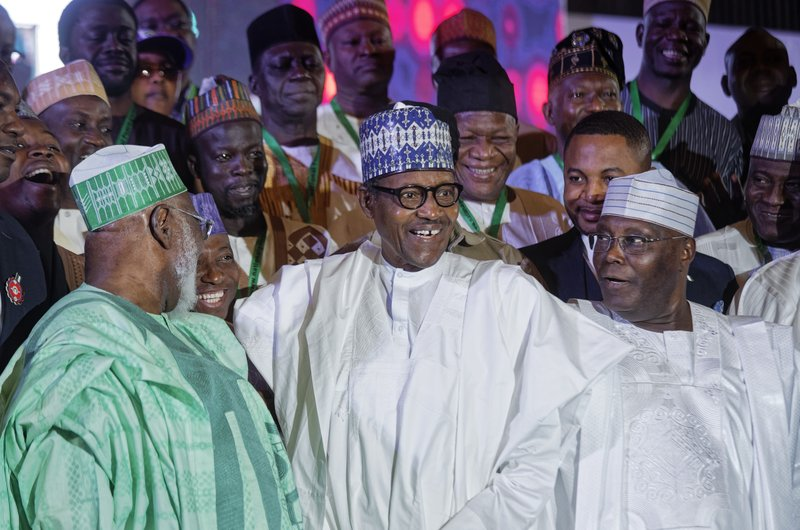 Incumbent President Muhammadu Buhari, center, and opposition presidential candidate Atiku Abubakar, right, stand for a group photo with other candidates after signing an electoral peace accord at a conference center in Abuja, Nigeria Wednesday, Feb. (AP Photo/Ben Curtis)