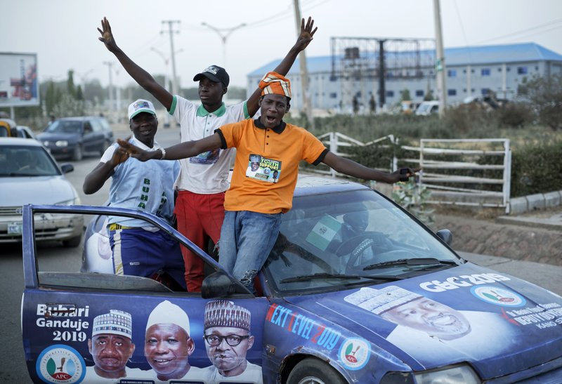Youth supporters of President Muhammadu Buhari cheer as they return from a rally of the ruling All Progressives Congress party, near the offices of the Independent National Electoral Commission in Kano, northern Nigeria Thursday, Feb. (AP Photo/Ben Curtis)