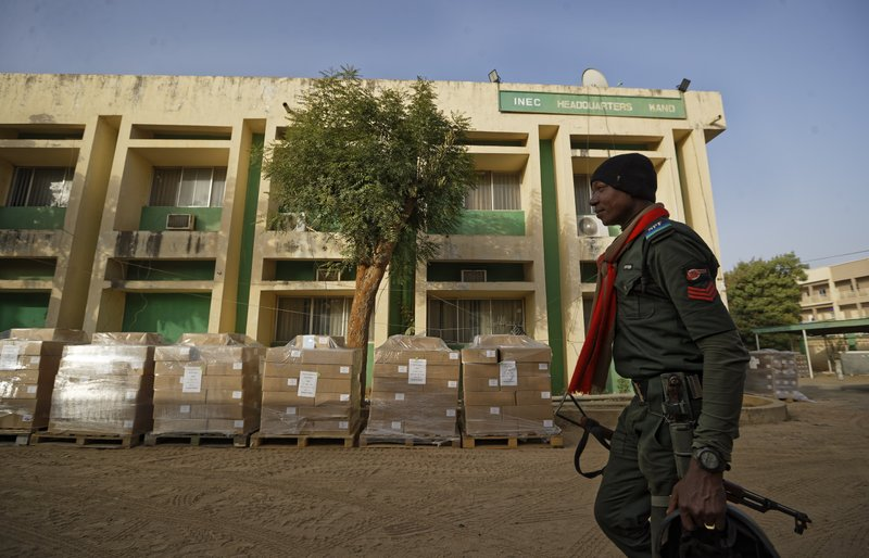 A Nigerian policeman provides security at the offices of the Independent National Electoral Commission in Kano, northern Nigeria Thursday, Feb. (AP Photo/Ben Curtis)