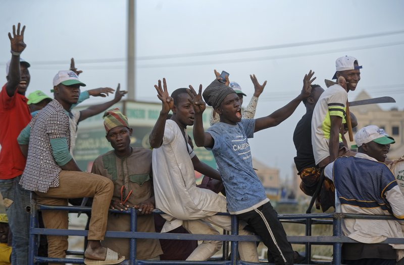 Youth cheer as they ride on the back of a truck returning from a rally of the ruling All Progressives Congress party, near the offices of the Independent National Electoral Commission in Kano, northern Nigeria Thursday, Feb. (AP Photo/Ben Curtis)