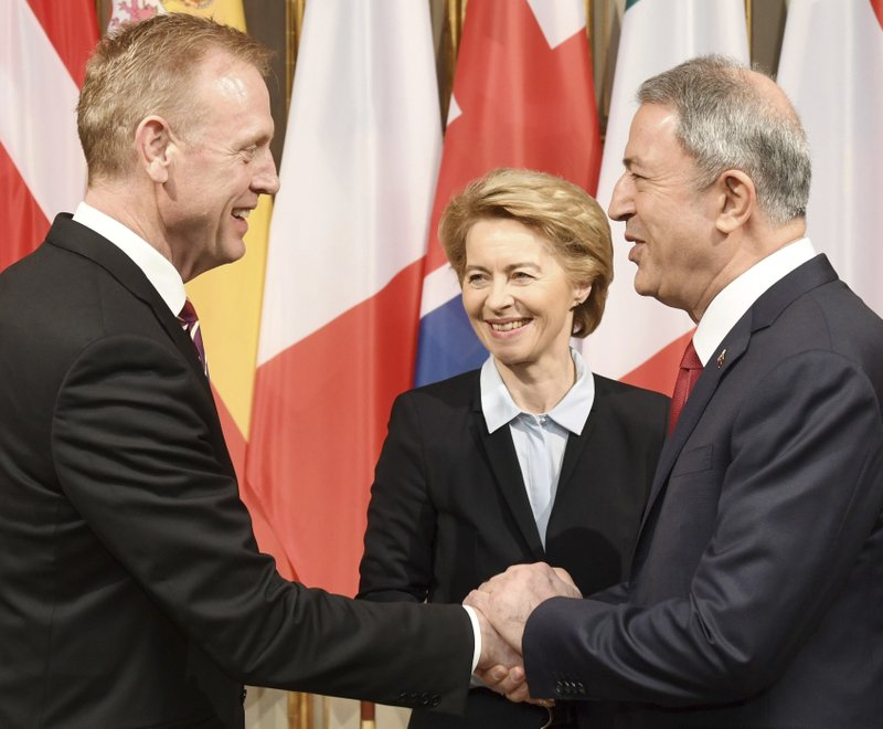 German minster of Defense Ursula von der Leyen, center, smiles when United States Secretary of Defense Patrick Shanahan, left, shakes hands with the Turkish minster of Defense Hulusi Akar, right, during the International Security Conference in Munich, Germany, Friday, Feb. (Tobias Hase/dpa via AP)