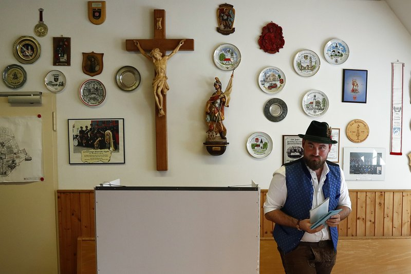 FILE - In this Sunday, Oct. 14, 2018 file photo a young man in traditional Bavarian clothes casts his vote for the Bavarian state elections at a poling station in Maisach, southern Germany. (AP Photo/Matthias Schrader)