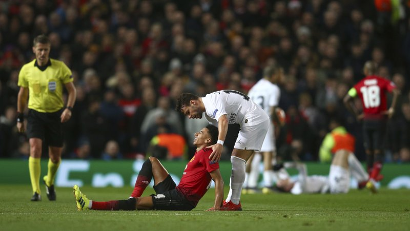 Manchester United's Jesse Lingard, lies injured as Paris Saint Germain's Juan Bernat leans over to help during the Champions League round of 16 soccer match between Manchester United and Paris Saint Germain at Old Trafford stadium in Manchester, England, Tuesday, Feb. (AP Photo/Dave Thompson)