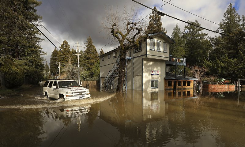 Drake Road is flooded by the Russian River at the Pee Wee Golf and Arcade of Guerneville, Calif., Thursday, Feb. (Kent Porter/The Press Democrat via AP)