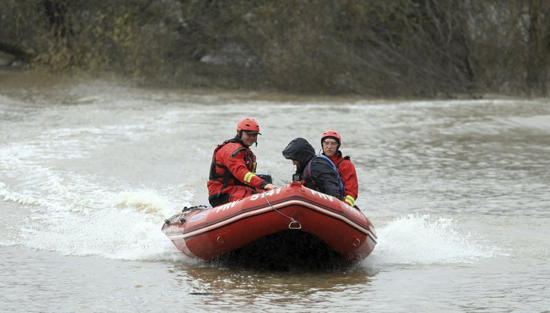Forestvillle Fire Protection District firefighters Mike Pierson, left, and Eric Gramola rescue a counselor from the Sonoma County Juvenile Probation Camp off Trenton Healdsburg Road in Forestville, Calif. (Kent Porter/The Press Democrat via AP)