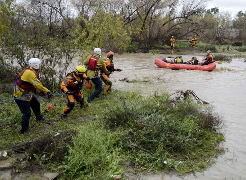 A San Bernardino County Fire swift rescue team rescues people stranded on an island in the rain swollen Santa Ana River bed Thursday, Feb. (Will Lester/The Orange County Register via AP)