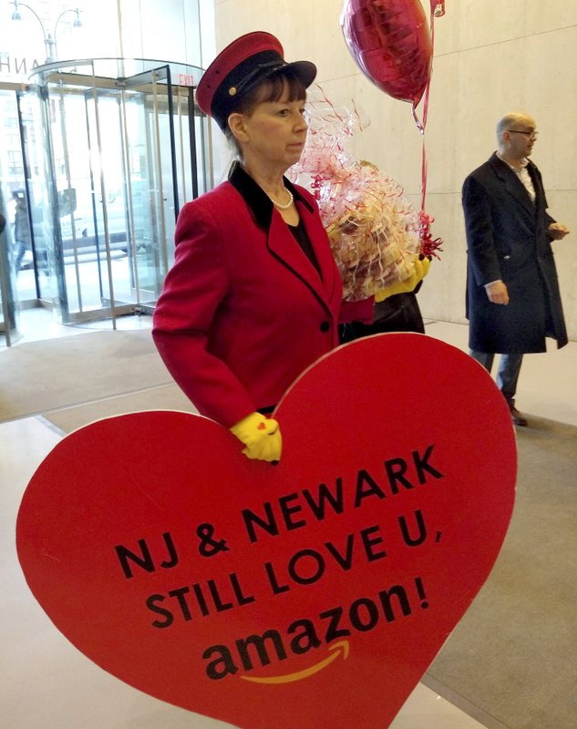 """In this Feb. 14, 2019 photo provided by Newark Alliance, Laurie Ross, an actor with the event planners at Life 'O the Party, holds a message reading """"NJ & Newark Still Love U, Amazon!"""" while arriving at an Amazon office in New York. (Matthew Cossel/Winning Strategies for Newark Alliance via AP)"""