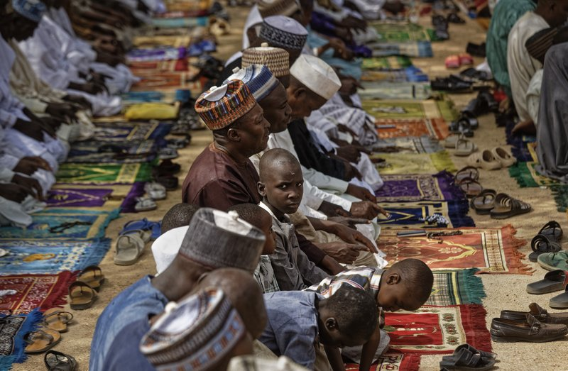 Muslims make traditional Friday prayers at a mosque near to the Emir's palace in Kano, northern Nigeria Friday, Feb. (AP Photo/Ben Curtis)