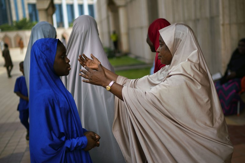 A Nigerian woman attends Friday prayers at the central mosque is security checked a day prior to the election, in Abuja, Nigeria, Friday Feb. (AP Photo/Jerome Delay)