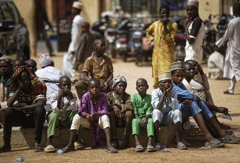 Young Muslim boys wait for traditional Friday prayers to begin at a mosque near to the Emir's palace a day prior to the start of the elections, in Kano, northern Nigeria, Friday, Feb. (AP Photo/Ben Curtis)