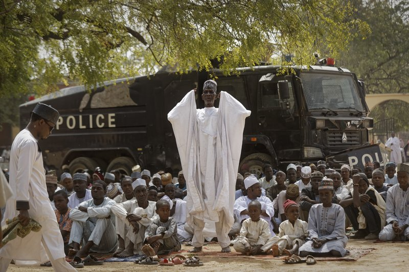 Muslims make traditional Friday prayers in front of a police riot truck, providing security due to the ongoing general threat of attacks by Islamic extremist group Boko Haram, at a mosque near to the Emir's palace in Kano, northern Nigeria, Friday, Feb. (AP Photo/Ben Curtis)
