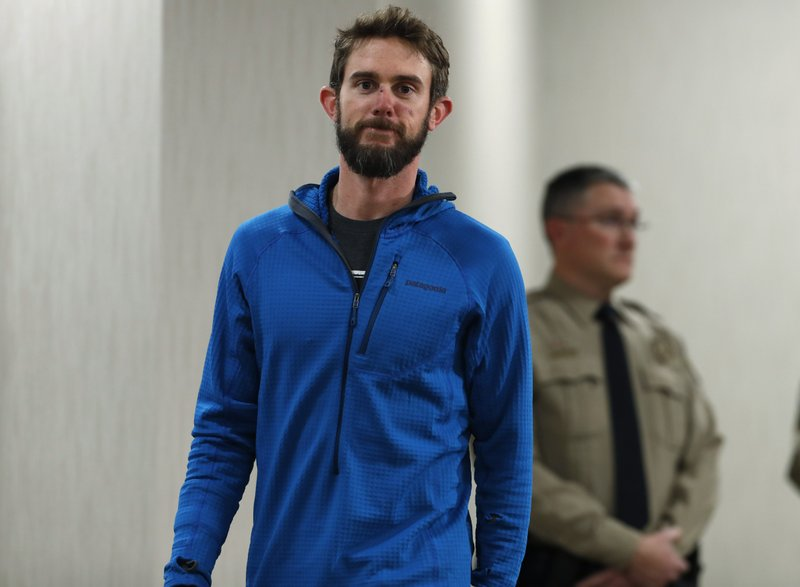 Travis Kauffman heads into a news conference Thursday, Feb. 14, 2019, in Fort Collins, Colo., about his encounter with a mountain lion while running a trail just west of Fort Collins last week. (AP Photo/David Zalubowski)