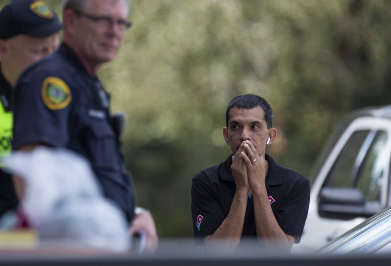 A man watches as the Houston Police officers investigate the scene of a fatal shooting at the Dunkin' Donuts on the 5800 block of Memorial Drive Friday, Feb. (Godofredo A. Vasquez/Houston Chronicle via AP)