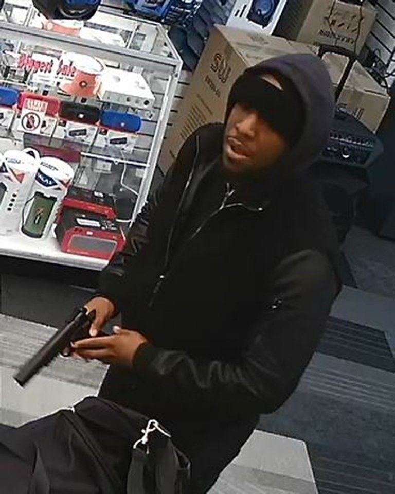 In this image taken from surveillance video provided by the New York Police Department, a man, identified by police as Christopher Ransom, is shown robbing a cell phone store, Saturday, Jan. (AP Photo/NYPD)