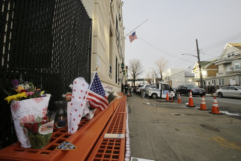 A makeshift memorial is placed near the 102nd precinct Wednesday, Feb. 13, 2019, in New York. Brian Simonsen, a New York City police detective was shot and killed by friendly fire Tuesday night as officers confronted a robbery suspect who turned out to be armed with a replica handgun, Commissioner James O'Neill said. (AP Photo/Frank Franklin II)