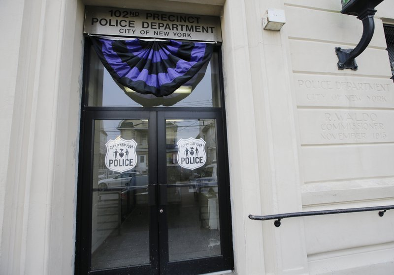 The entrance to the 102nd precinct is shown Wednesday, Feb. 13, 2019, in New York. A New York City police detective was shot and killed by friendly fire Tuesday night as officers confronted a robbery suspect who turned out to be armed with a replica handgun, Commissioner James O'Neill said. (AP Photo/Frank Franklin II)