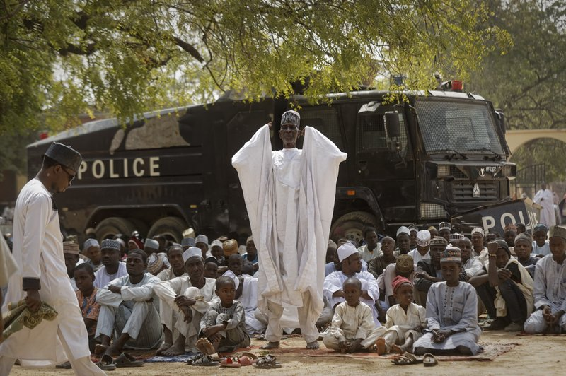 Muslims make traditional Friday prayers in front of a police riot truck, providing security due to the ongoing general threat of attacks by Islamic extremist group Boko Haram, at a mosque near the Emir's palace in Kano, northern Nigeria, Friday, Feb. (AP Photo/Ben Curtis)