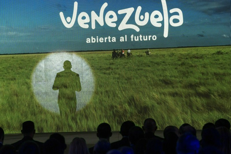 The shadow of Venezuela's Communications Minister Jorge Rodriguez is cast on a screen while presenting the country's strategy to promote tourism in all its regions, in the Hotel Alba Caracas, in Caracas, Venezuela, Monday, Feb. (AP Photo/Rodrigo Abd)