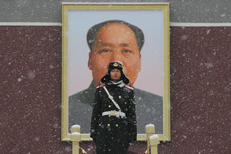 A paramilitary police officer stands guard under the portrait of former leader Mao Zedong outside Tiananmen Gate as snow falls in Beijing, Tuesday, Feb. (AP Photo/Andy Wong)