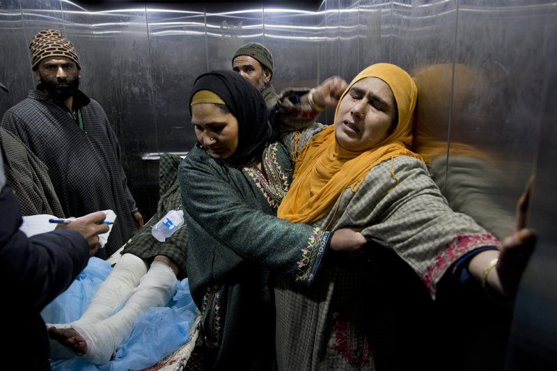 A Kashmiri woman is comforted by another as a young wounded relative is taken for treatment inside a hospital Srinagar Indian-controlled Kashmir, Wednesday, Feb. (AP Photo/ Dar Yasin)