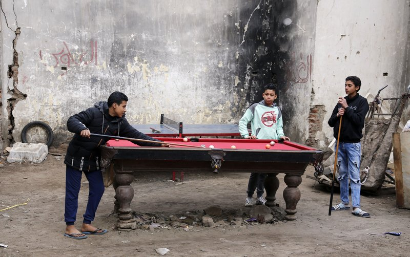 Boys play billiards as they rent a table for 4 Egyptian Pounds (U.S. $0.25), at Darb Shughlan, a popular district in Cairo, Egypt, on Friday, Feb. (AP Photo/Amr Nabil)