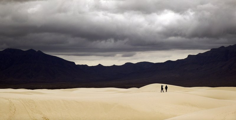 Visitors walk across dunes at White Sands National Monument as a rain storm passes, Sunday, Feb. 10, 2019, near Alamogordo, N. (AP Photo/Eric Gay)
