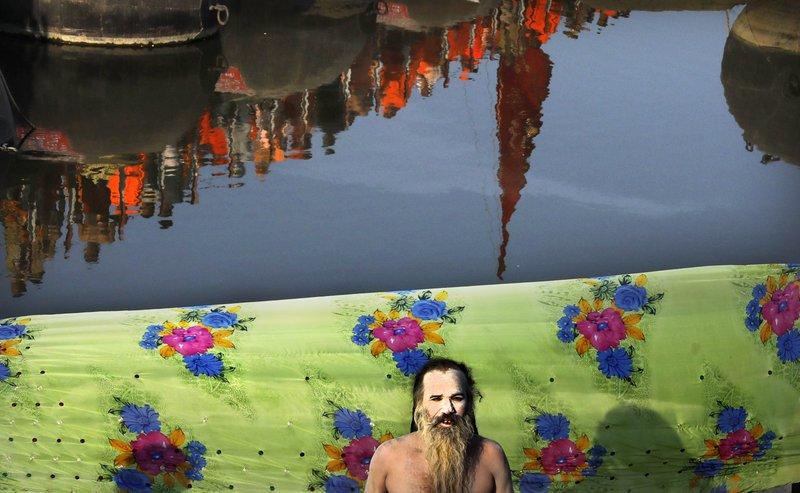 A naked Hindu holy man prays as others cross a pontoon bridge to take ritualistic dip on the auspicious day of Basant Panchami at Sangam, the confluence of sacred rivers the Yamuna, the Ganges and the mythical Saraswati, during the Kumbh Mela or the Pitcher Festival, in Prayagraj, Uttar Pradesh state, India, Sunday, Feb. (AP Photo/Rajesh Kumar Singh)