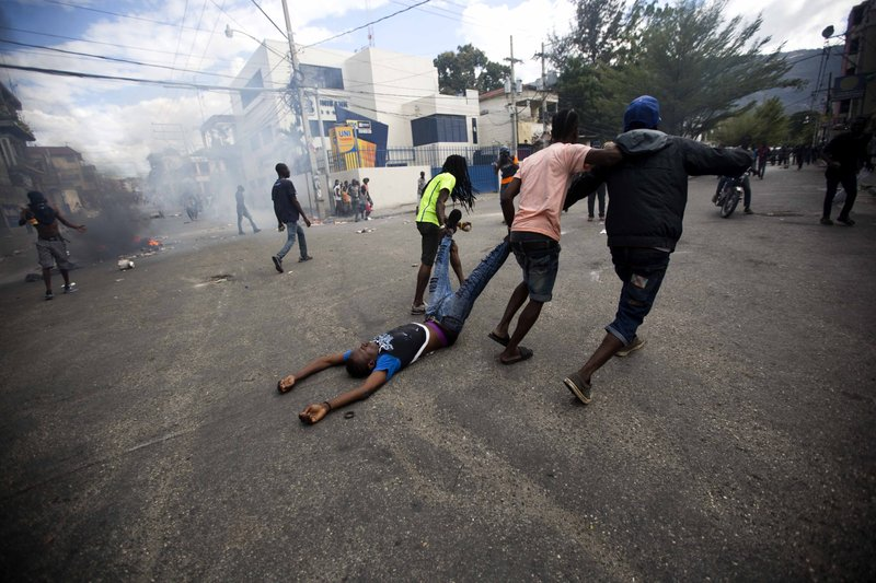Demonstrators drag the body of a fellow protester toward police, as a form of protest after police shot into the crowd in which he died, during a demonstration demanding the resignation of Haitian President Jovenel Moise near the presidential palace in Port-au-Prince, Haiti, Tuesday, Feb. (AP Photo/Dieu Nalio Chery)
