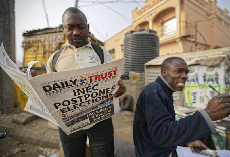 A man reads a copy of a newspaper which managed to print the news of the postponement in time, in the morning at a newspaper stand in Kano, in northern Nigeria Saturday, Feb. (AP Photo/Ben Curtis)